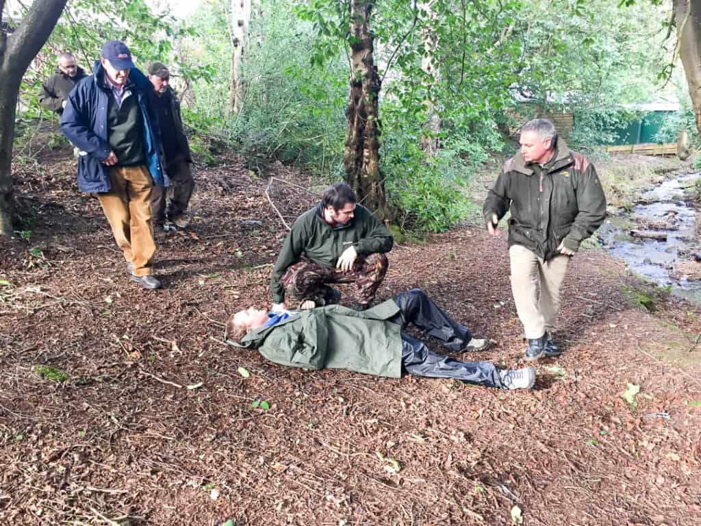 forestry first aid course with stalkers in a wood looking at a simulated casualty