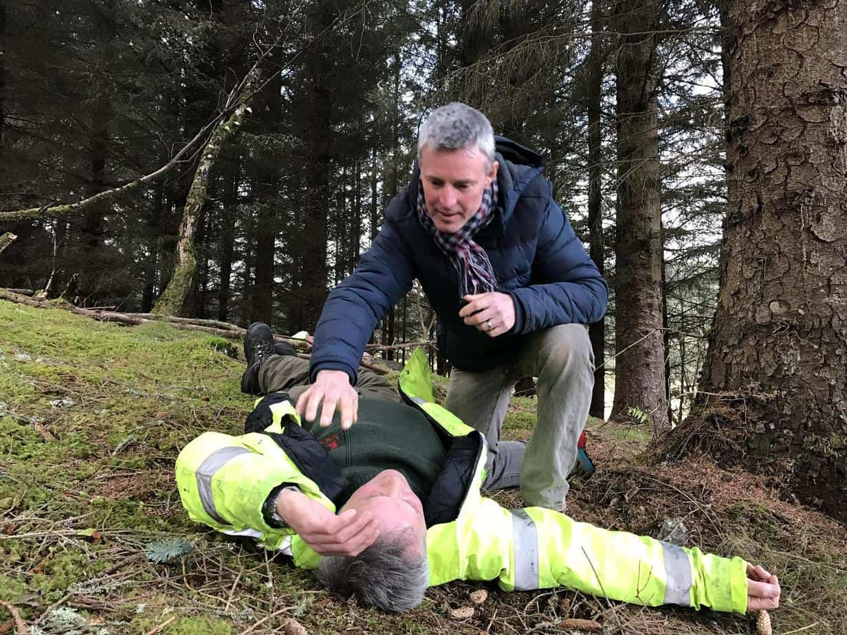 person checking to see if a casualty is ok during a forestry first aid course