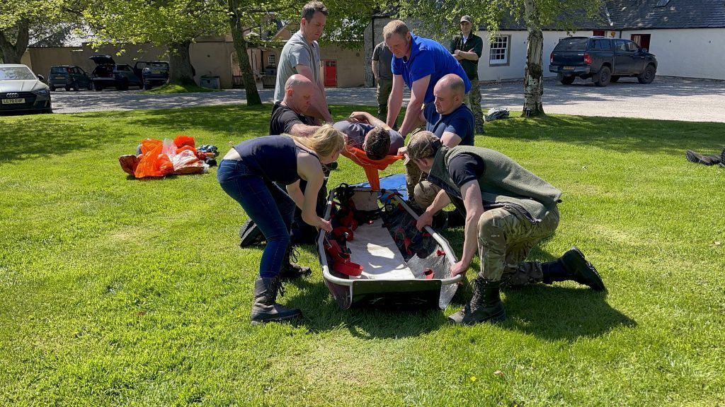 practicing an improvised stretcher with estate staff in the Scottish highlands during efaw+F course